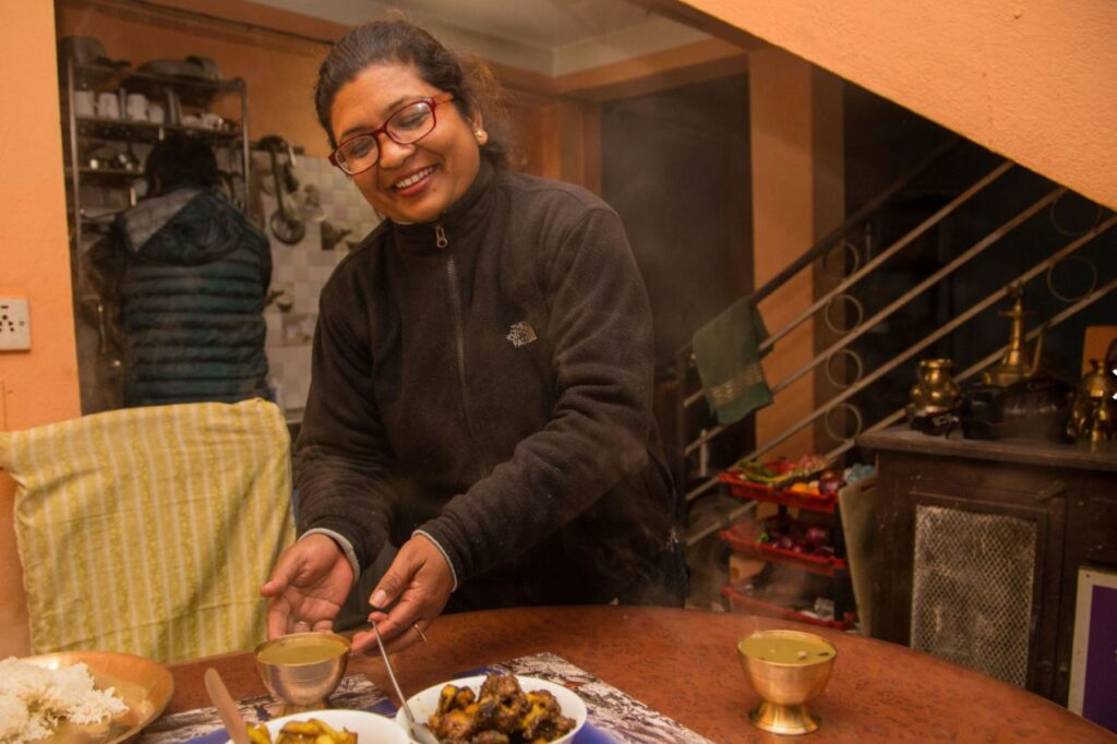 Local woman serving dinner at Panauti Community Homestay